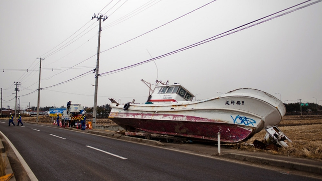 Workers from a power company repair damaged power lines in an area affected by the tsunami in the Yuriage area of Natori