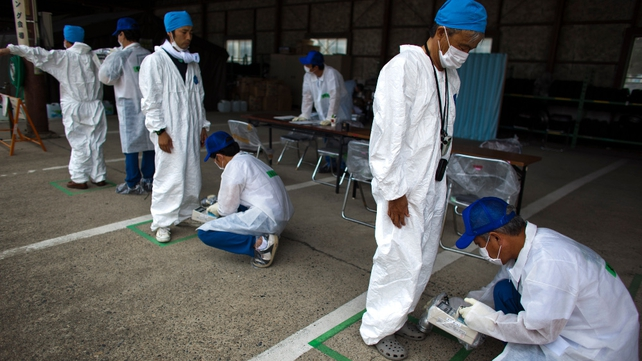 Residents who live in the 20km exclusion zone around the Fukushima nuclear plant undergo a radiation screening test