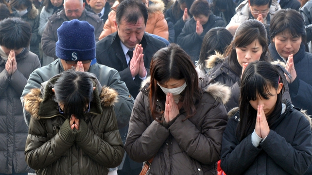 People offer a silent prayer for victims in front of a memorial at the Okawa elementary school in Ishinomaki