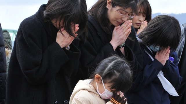 A family prays for tsnuami victims