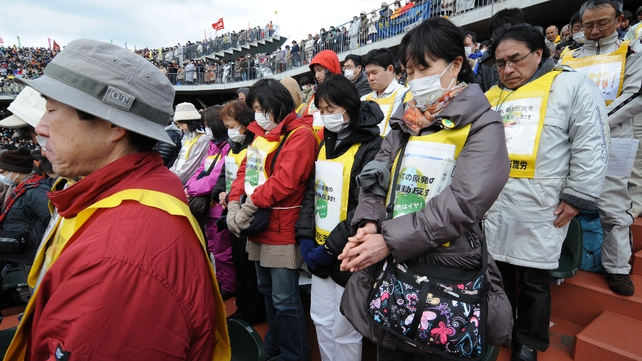 People offer silent prayers for victims during a rally denouncing nuclear power plants in Koriyama, Fukushima Prefecture