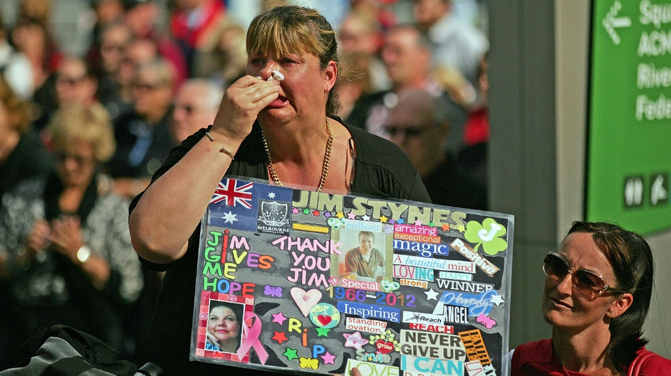 A woman cries as she watches the television broadcast outside of the state funeral at St Paul's Cathedral