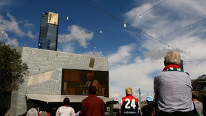 Crowds watch the service on a big screen at Federation Square