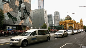 The funeral procession heads down Finders Street en route to a scheduled stop at the Melbourne Cricket Ground