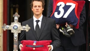 Media personality Jules Lund carries the Brownlow Medal of Jim Stynes, won in 1991