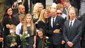 Family and relatives watch as Jim Stynes' coffin is loaded into the hearse
