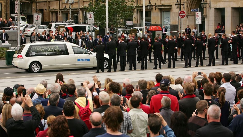 Melbourne players, wearing the club blazers that Jim Stynes had presented to them only days before he died, form a guard of honour as the hearse drives down Swanston Street