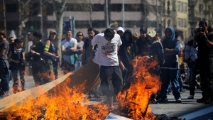 A demonstrator sets fire to a barricade during rioting as a 24-hour strike is called in Barcelona