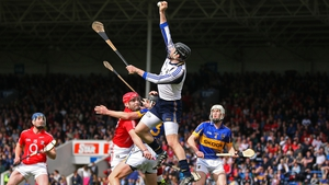Tipperary goalkeeper Brendan Cummins fields a dangerous ball as team-mate Paul Curran holds off the attentions of Cork's Paudie O'Sullivan during the drawn game at Semple Stadium