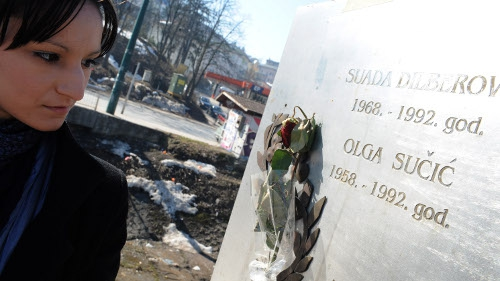 A local woman looks at a plaque in memory of the first two war victims at a bridge in central Sarajevo