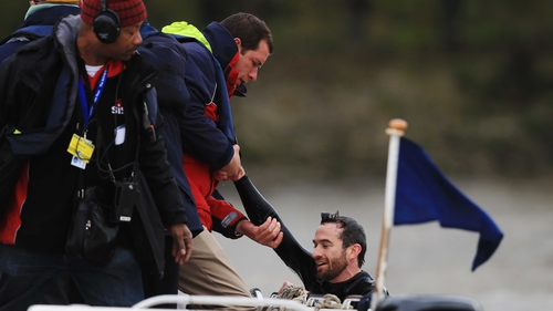 Trenton Oldfield is pulled from the water after swimming in front of the crews and disrupting the Xchanging University Boat Race between Oxford and Cambridge