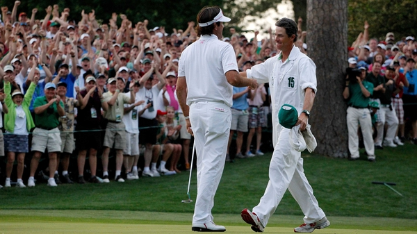 Bubba Watson celebrates with his caddie following his play-off victory at the 10th hole