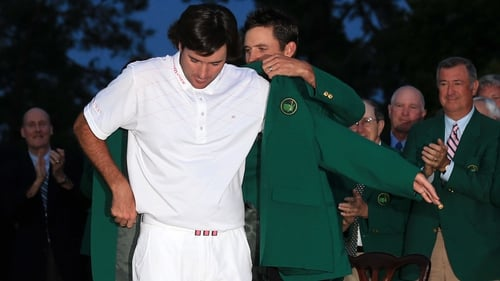 Last year's Masters champion Charl Schwartzel helps Watson try on his Green Jacket