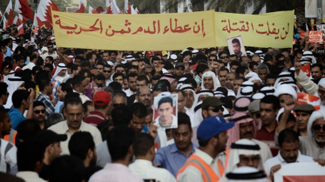 Bahrain protesters in Manama carry a banner which reads: 'The killers will not go away'.