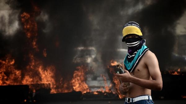 A protester lights a petrol bomb near a police barricade in Manama