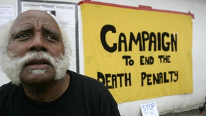An anti-death penalty activists sits near a sign at the entrance of San Quentin State Prison in 2005