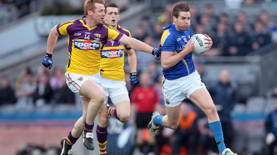 Longford's Niall Mulligan breaks through under the watchful eye of Wexford's Eric Bradley