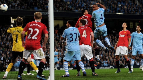 Vincent Kompany rises highest to power home a first-half header to give City victory in the Manchester derby