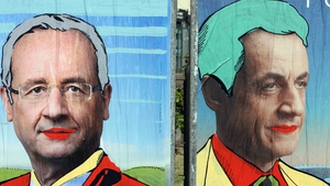 Graffiti tagged on official campaign posters of Francois Holland (L) and incumbent president Nicolas Sarkozy