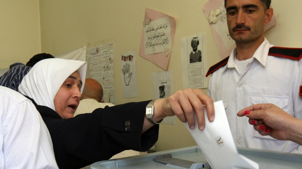 A Syrian woman casts her vote in the country's parliamentary election