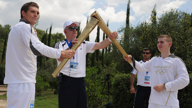 Alex Loukas from Britain lights the London 2012 Olympic Torch from Spyros Gianniotis of Greece