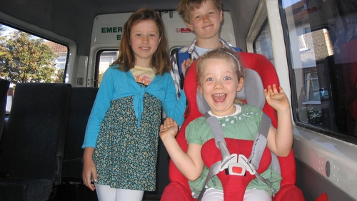Grace on the bus with sister Martha and brother Sean on the way to school at the CRC