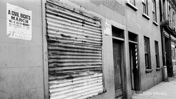 A boarded-up premises in Derry city on 7 May 1969. A notice publicising a civil rights march is visible. (C) RTÉ Stills 2142/022