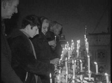 People praying and lighting candles in a vigil for peace at St. Eugene's Cathedral, Derry.