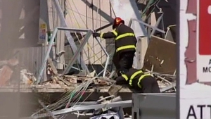Rescuers search through rubble of collapsed buildings