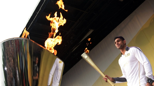 Boxer Amir Khan lights the cauldron with the Olympic Flame at the end of the relay leg through Bolton