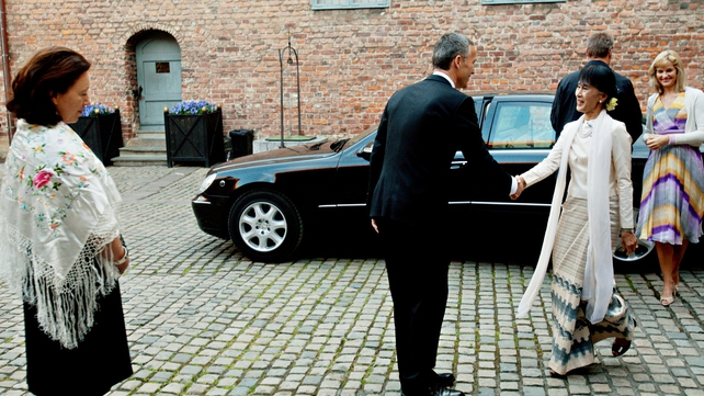 Norwegian Prime Minister Jens Stoltenberg welcomes Aung San Suu Kyi as she arrives to attend a dinner in her honour