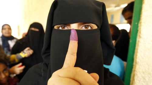 An Egyptian women shows her ink-stained finger after voting at a polling station in Cairo