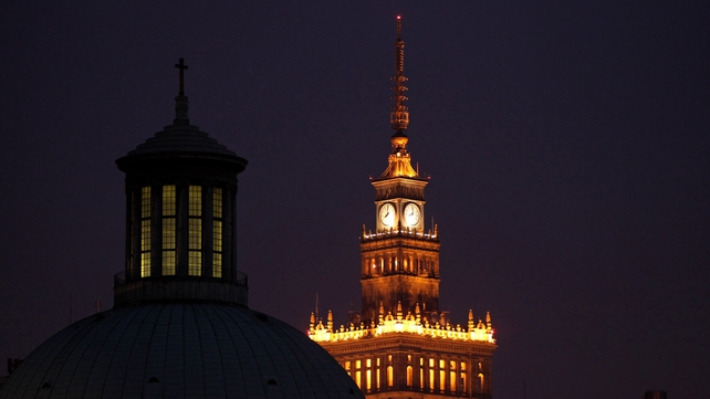 The Palace of Culture and Science (right) stands illuminated behind the Holy Trinity Church of the Augsburg Confession