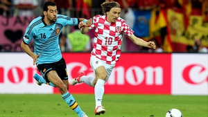 Croatia's Luka Modric shields possession from Sergio Busquets of Spain