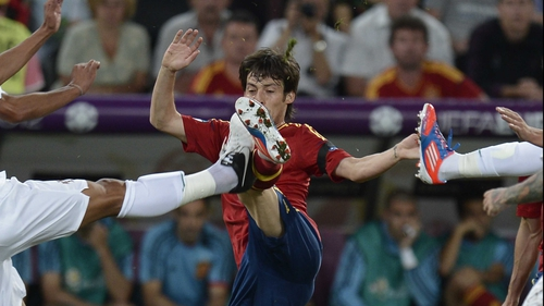 Spain's David Silva battles for possession with two Portuguese players