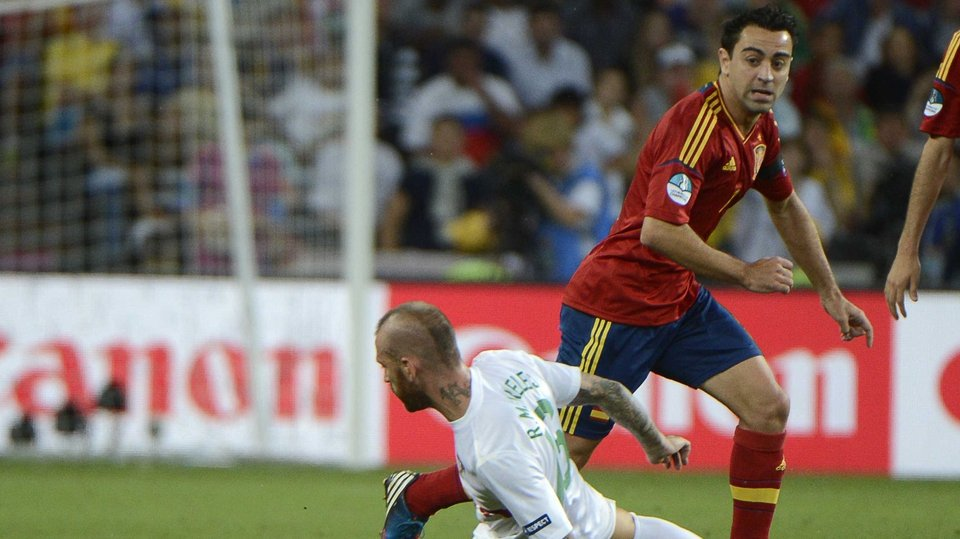 Spain's Xavi skips past Portugal midfielder Raul Meireles
