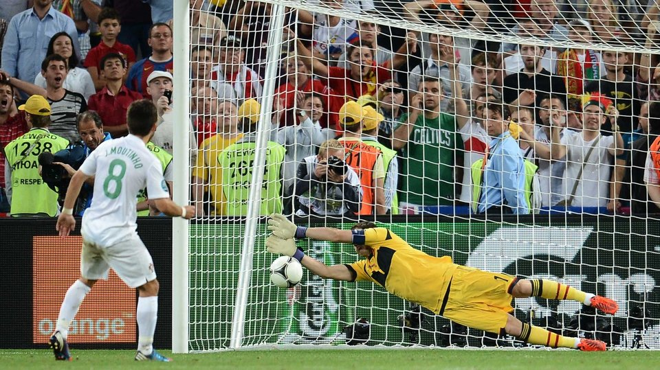 Spanish goalkeeper Iker Casillas saves from Joao Moutinho
