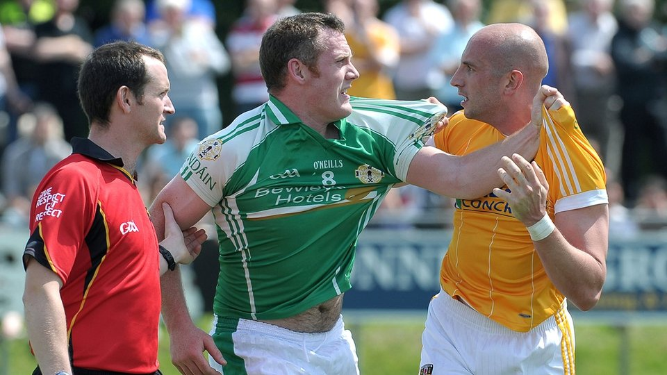 Tempers flare as a linesman has to step in and seperate London's Lorcan Mulvey and Conal Kelly of Antrim