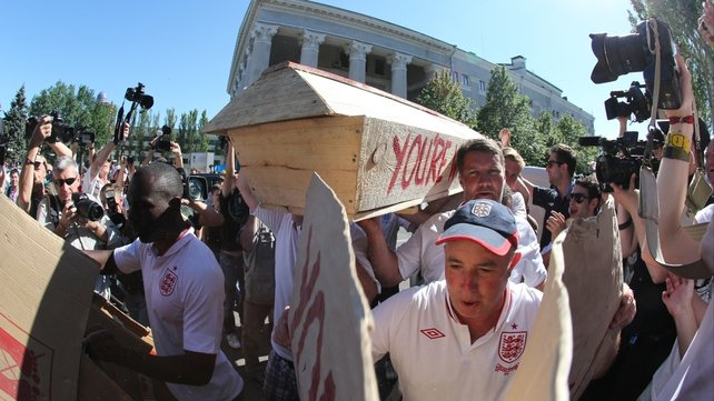 English fans carry a coffin painted with a St George's Cross and with the words 'You're wrong Campbell' painted on the side in Donetsk