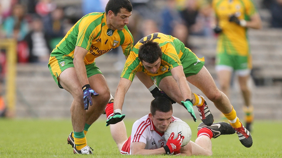Tyrone's Aidan McCrory is tackled by Frank McGlynn and David Walsh of Donegal