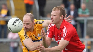 Cork's Michael Shields gets his handpass away despite the best efforts of Michael O'Shea of Clare