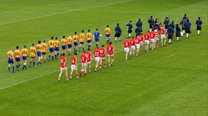 The Cork and Clare teams line-up for the pre-match parade at Gaelic Grounds