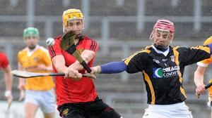 Antrim goalkeeper Padraig Nugent seeks to block Down's Caolan Bailie