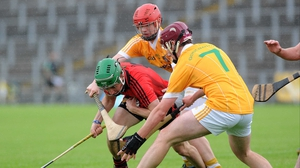 Antrim's Paddy Burke and Ryan Gillan surround Down's James McGrath in the drawn Ulster minor hurling final