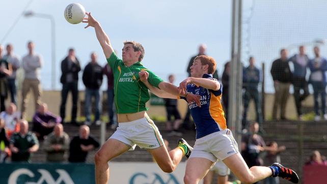 Shane Moran of Leitrim fields the ball under pressure from Wicklow's Peadar Burke