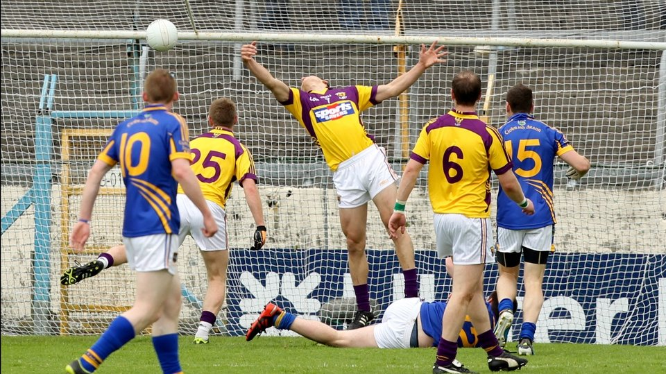 Wexford's Lee Chin is unable to prevent the opening goal of the game scored by Donagh Leahy (on ground) of Tipperary