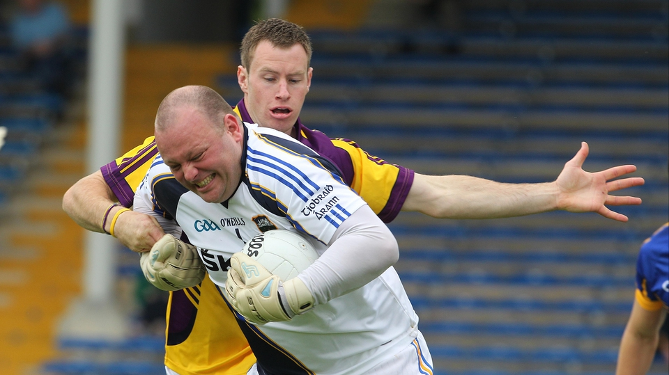 Tipperary goalkeeper Paul Fitzgerald bursts through the tackle of Wexford's Paddy Byrne