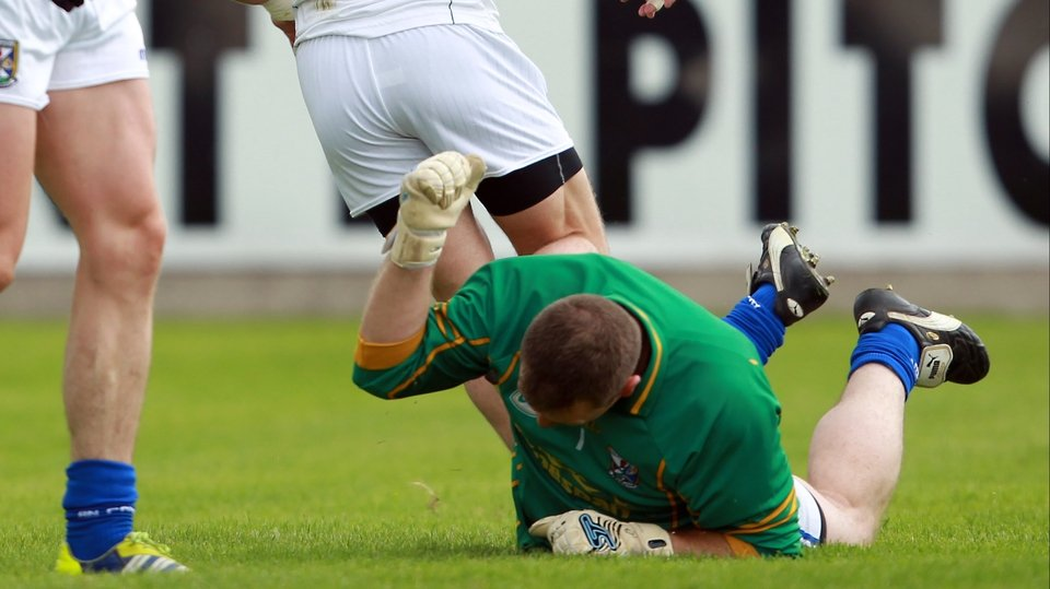 Cavan goalkeeper Jame Reilly beats the ground in frustration as Emmet Bolton of Kildare scores the Lilywhites' second goal