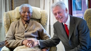 Former US president Bill Clinton poses with Nelson Mandela on the eve of his 94th birthday in 2012