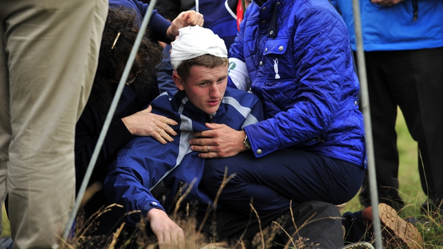 Jason Blue receives attention after he was struck by Rory McIliroy's ball yesterday